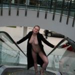 Naked wife on mall escalator in open front coat